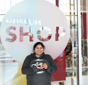 Holly Sabourin standing in front of the sign for the Royal Alberta Museum gift shop