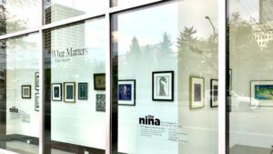 Window display featuring several paintings and prints