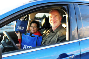 "Two people sitting in the front seats of a blue car. They are smiling and holding blue reusable bags that say ""ATB"""