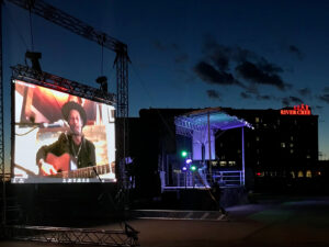 "Large outdoor screen with Barney Bentall. He is wearing a hat and playing a guitar. In the background is the River Cree Hotel with a red neon sign that says ""River Cree"""