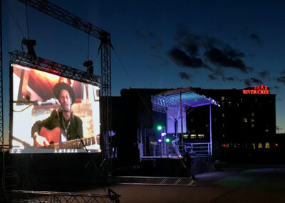 """Large outdoor screen with Barney Bentall. He is wearing a hat and playing a guitar. In the background is the River Cree Hotel with a red neon sign that says """"River Cree"""""""