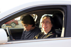 Two people sitting in the front seats of a silver car with the window rolled down, smiling at the camera