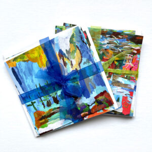 Two sets of colourful square greeting cards tied with ribbons