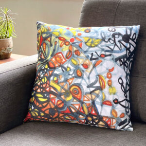 Square pillow featuring an orange, blue, and yellow painting by Uli Rossier on a grey couch