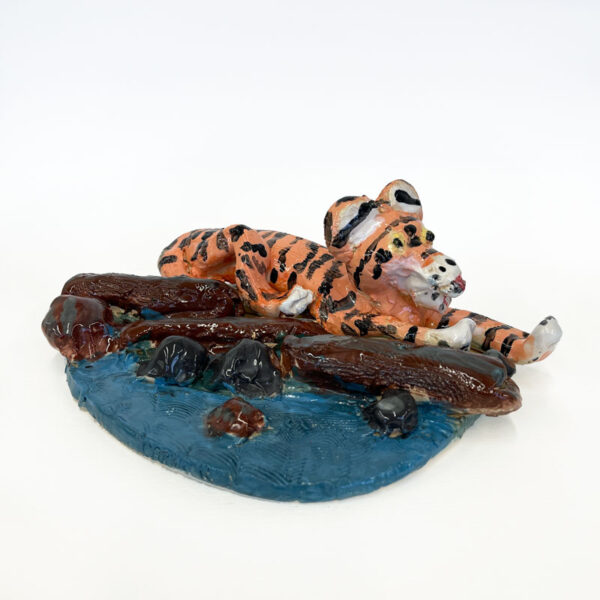 Ceramic sculpture of a tiger laying by a river by Carrie Reed