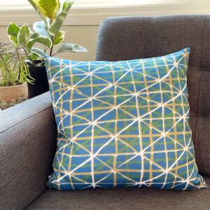 Teal square pillow with white and yellow geometric design