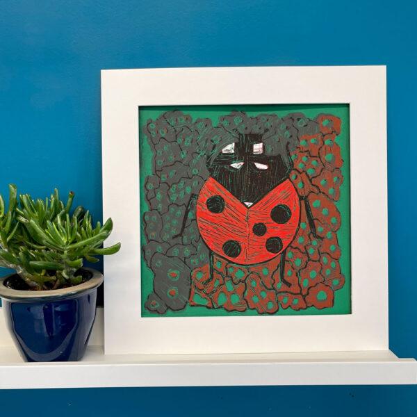 Lady Bug linocut in a white mat on a shelf